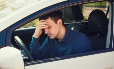 Casual young guy driver experiencing headache, should stop the car after driving in a traffic jam at rush hour. Exhausted, overloaded man keeps hand to head, healthcare concept, feeling anxiety.